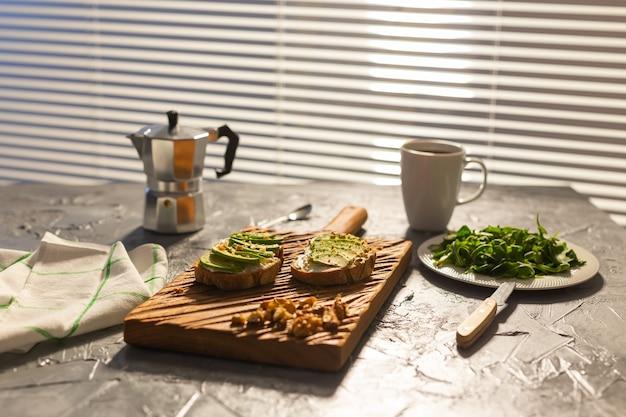 Tranches d'avocat sur du pain grillé avec des noix et des épinards au café sur une assiette et petit-déjeuner moka pot et
