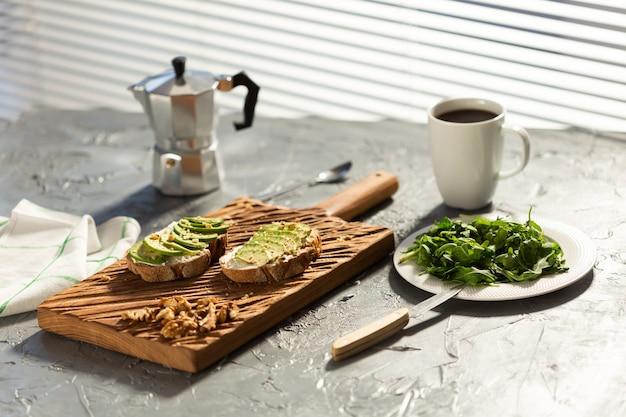 Tranches d'avocat sur du pain grillé avec des noix et des épinards de café sur une assiette et petit-déjeuner pot moka et