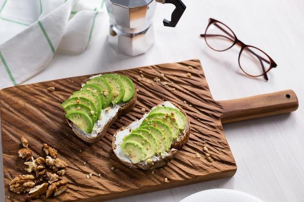 Tranches d'avocat sur du pain grillé avec des noix. petit-déjeuner et concept de nourriture saine.