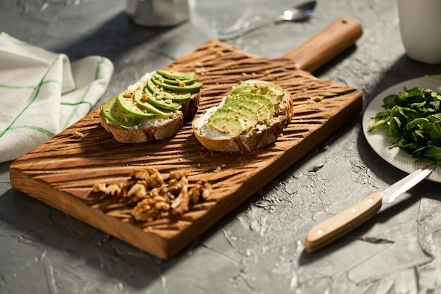 Tranches d'avocat sur du pain grillé avec des noix. petit-déjeuner et nourriture saine