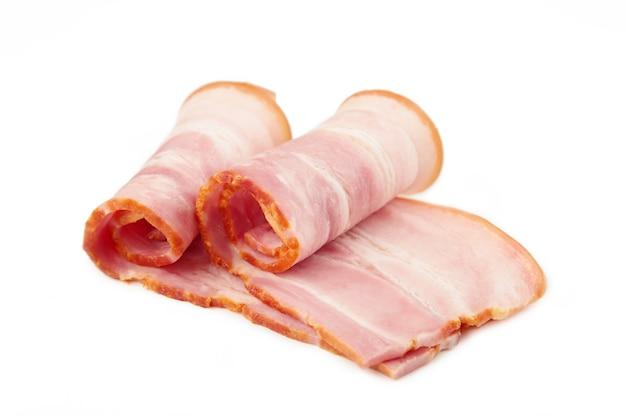 Tranches de bacon cru frais isolé sur fond blanc. rouleau de bacon. vue de dessus