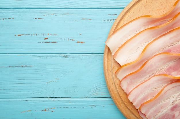 Tranches de bacon cru frais sur la planche à découper en bois sur bleu