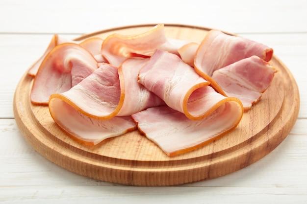 Tranches de bacon cru frais sur la planche à découper en bois isolé