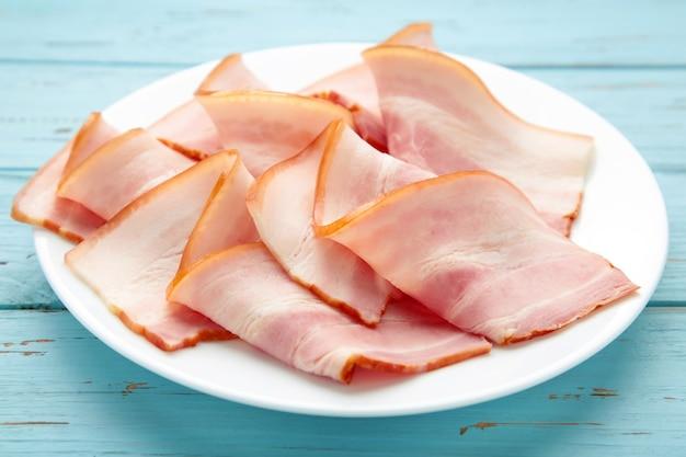 Tranches de bacon cru frais sur plaque sur fond de bois bleu. vue de dessus