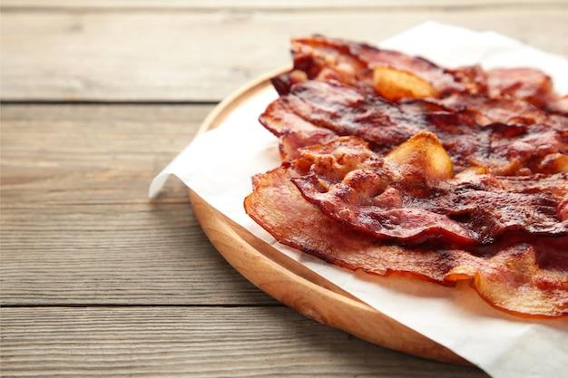 Tranches de bacon frites sur une planche à découper