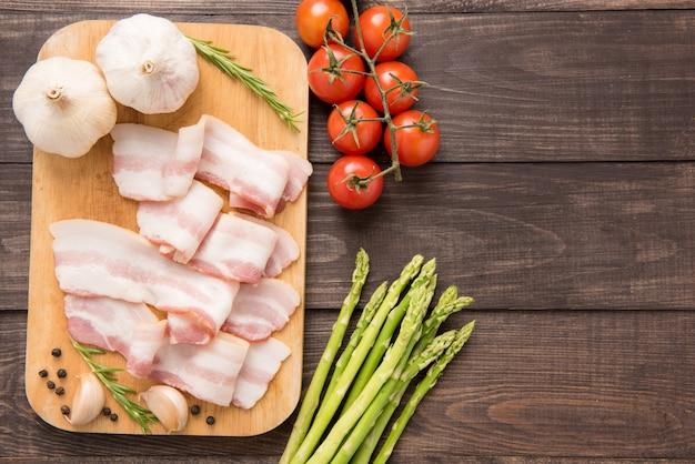 Tranches de bacon fumé sur une table en bois. vue de dessus