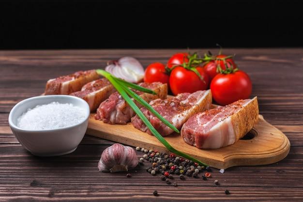 Tranches de bacon de porc cru sur une planche à découper, sur une table en bois rurale. poitrine de porc