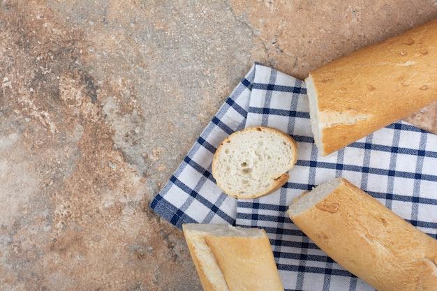 Tranches de baguette fraîche sur nappe à rayures