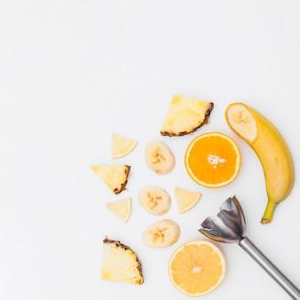 Des tranches de banane; ananas; oranges coupées en deux avec un mélangeur à main sur fond blanc