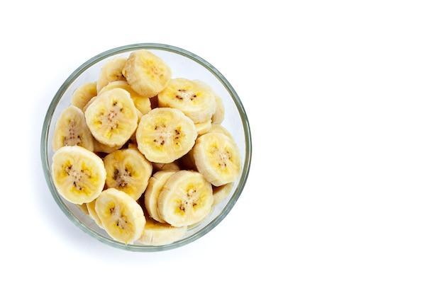 Tranches de banane dans un bol en verre sur fond blanc.