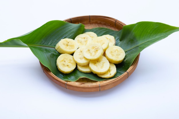 Tranches de banane dans un panier en bambou sur fond blanc.