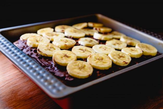 Tranches de banane sur un gâteau sur un plateau avant de le cuire.