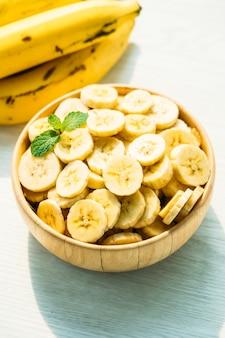 Tranches de banane jaune dans un bol en bois