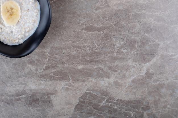 Tranches de banane mûre sur un bol de porridge, sur la surface en marbre