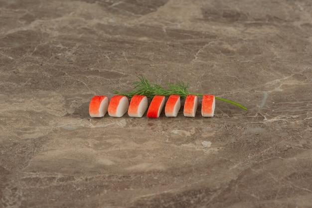 Tranches de bâtonnets de crabe avec des verts sur table en marbre.