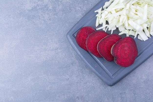 Tranches de betteraves rouges avec du chou blanc haché sur la planche