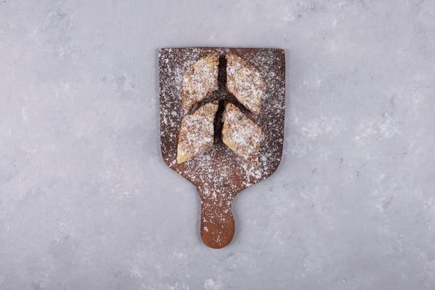 Tranches de biscuit avec de la farine sur un plateau en bois