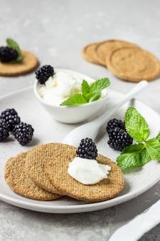Tranches de biscuits complets croustillants au fromage à la crème, à la mûre et à la menthe sur une assiette grise.