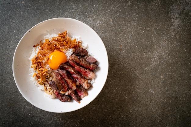 Tranches de boeuf sur un bol de riz garni d'oeuf