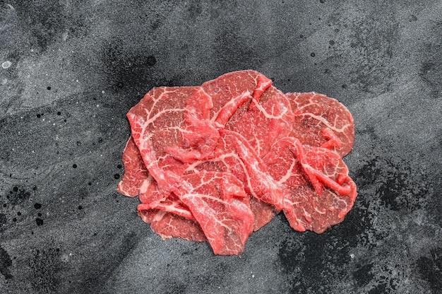 Tranches de boeuf capriccio, viande crue. fond noir. vue de dessus.