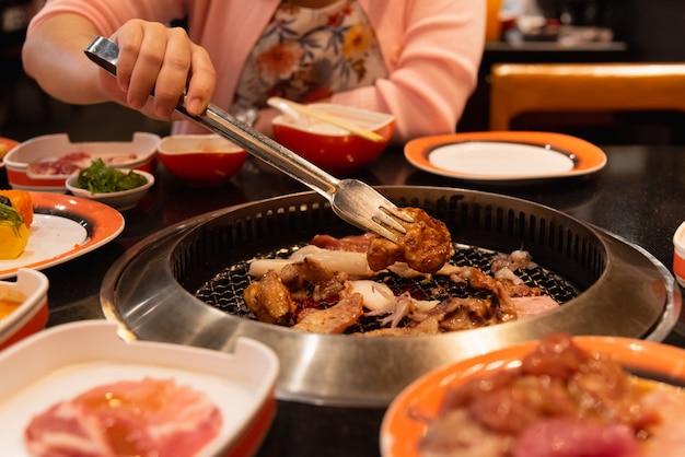 Tranches de bœuf et de porc crus sur une grille pour yakiniku à la japonaise ou au barbecue