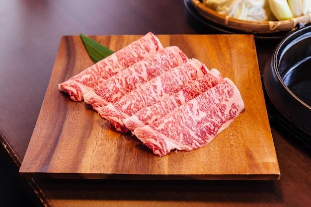 Tranches de boeuf rares de première qualité wagyu a5 à la texture marbrée élevée servies pour sukiyaki et shabu.