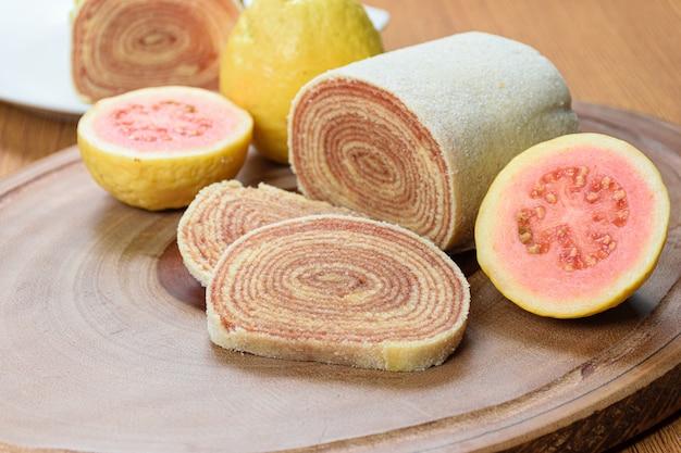 Tranches de bolo de rolo à côté de goyaves sur une planche de bois