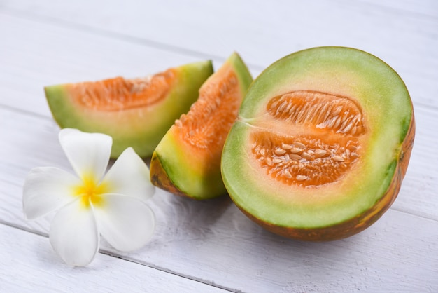 Tranches de cantaloup thaïlandais de fruits tropicaux asiatiques et de fleurs sur bois, cantaloup melon melon cucurbitaceae