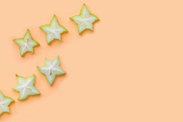 Tranches de carambole vertes sur fond de couleur pastel.