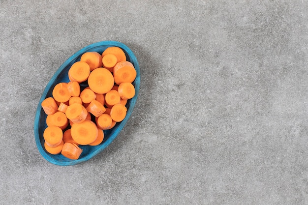 Tranches de carotte sur une assiette en bois, sur le marbre.