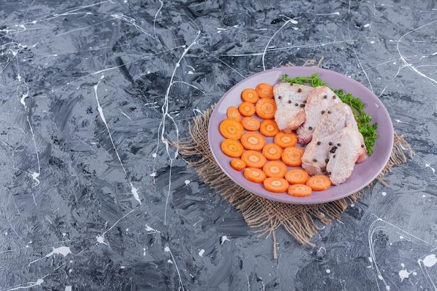 Tranches de carottes, ailes et verts sur une assiette sur une toile de jute, sur le bleu.