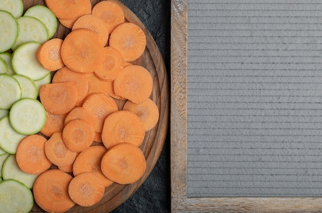 Tranches de carottes et courgettes sur plaque de bois. photo de haute qualité