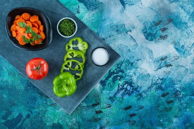 Tranches de carottes dans un bol à côté de légumes sur une serviette, sur le fond bleu.