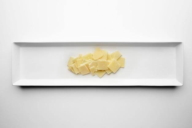 Tranches carrées de parmesan isolé sur plaque blanche au centre