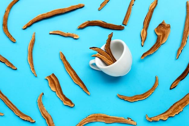 Tranches de champignons lingzhi séchés avec tasse sur fond bleu. vue de dessus