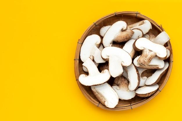 Tranches de champignons shiitake frais dans un panier en bambou sur fond jaune.