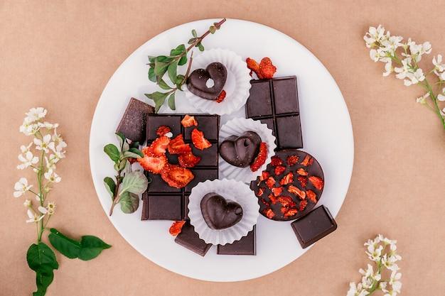 Des tranches de chocolat à la main et des bonbons sur une plaque blanche.concept de nourriture saine et de desserts
