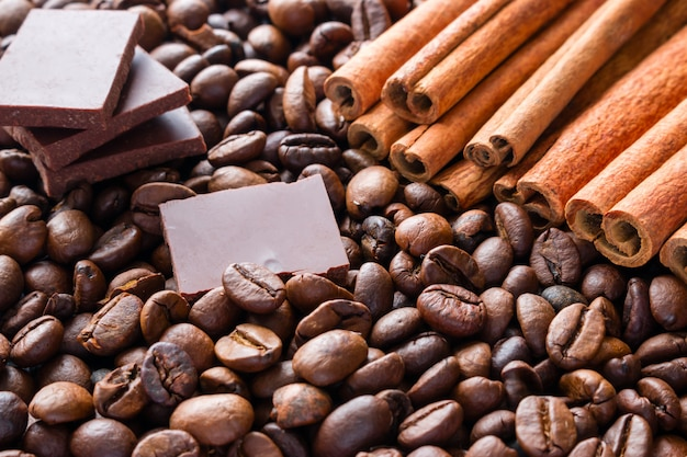 Tranches de chocolat noir sur des bâtons de cannelle et des grains de café