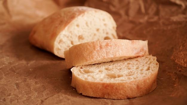 Tranches de ciabatta sur papier craft de délicieuses pâtisseries fraîches du pain frais fait maison
