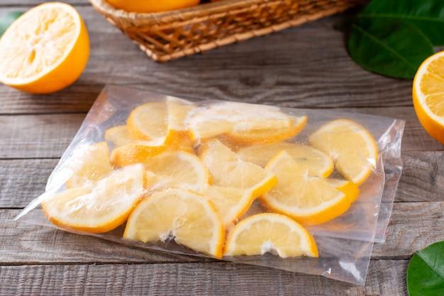 Tranches de citron congelé dans un sac sur une table en bois