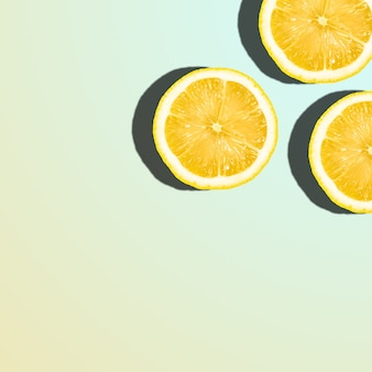 Tranches de citron sur dégradé pastel, agrumes tropicaux avec espace de copie