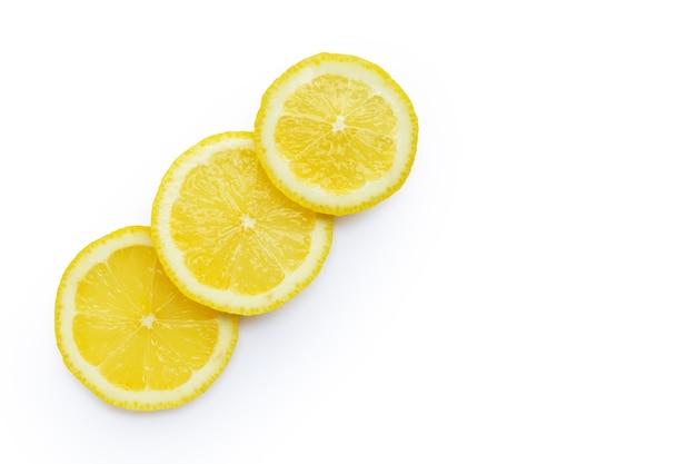 Tranches de citron frais isolés sur un mur blanc.