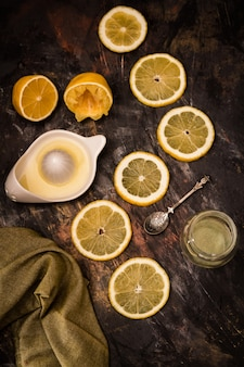 Tranches de citron mûres fraîches avec presse-agrumes et cuillère sur fond noir