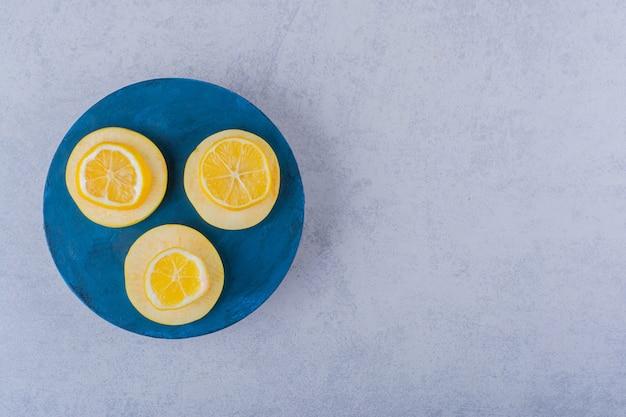 Tranches de citron et de pomme mûres fraîches sur planche bleue.