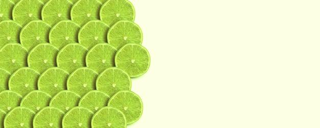 Tranches de citron vert sur fond jaune, image de maquette panoramique, fruits frais avec espace pour le texte