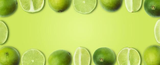 Tranches de citron vert sur fond vert clair, maquette panoramique, image créative avec espace pour le texte