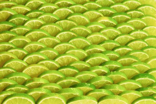 Tranches de citron vert frais en arrière-plan.