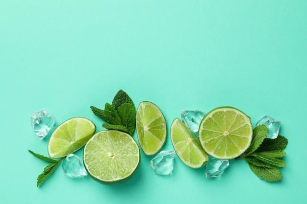 Tranches de citron vert, glaçons et feuilles de menthe sur fond de menthe