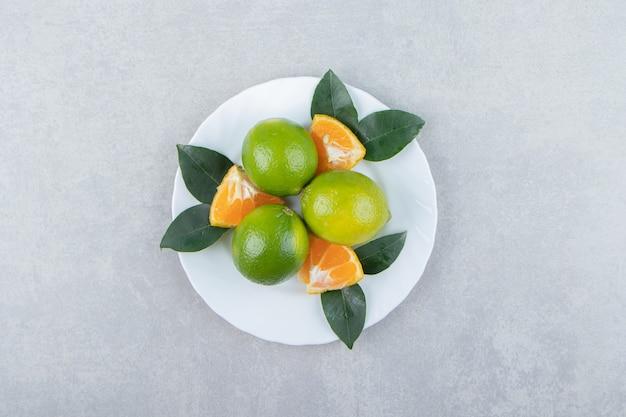 Tranches de citron vert et de mandarine sur plaque blanche.
