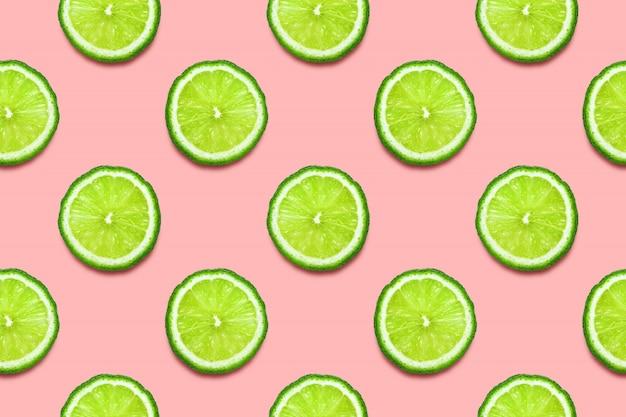 Tranches de citron vert. modèle sans couture sur rose pastel.